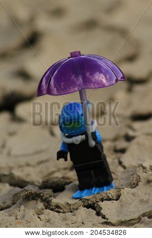 Figurine scuba diver with umbrella on parched ground/This is a detail of parched ground and figurine scuba diver with umbrella.