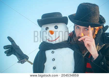 Snowman And Man In Gentlemen Hats And Scarves