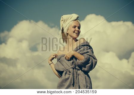 Happy woman in bathrobe and towel on head. Girl smiling on cloudy blue sky. Model with naked shoulders sunbathing on sunny day. Spa and wellness. Summer vacation concept vintage filter