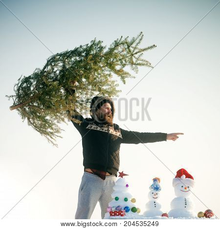 Hipster Raising Xmas Tree And Pointing Finger