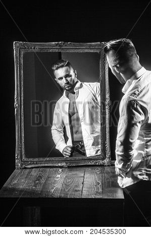 handsome muscular macho man or athlete guy with sexy body of bodybuilder with torso belly six packs has beard on serious face in pants white shirt near vintage mirror isolated on black background