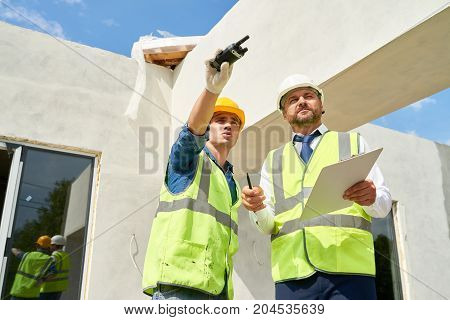 Low angle view of confident bearded businessman wearing suit and hardhat talking to young foreman while checking construction phase of building