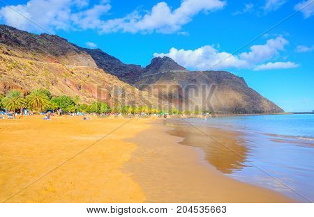 beach on the island of Tenerife in bright sunny day a great number of vacationers ashore on a background mountains tower