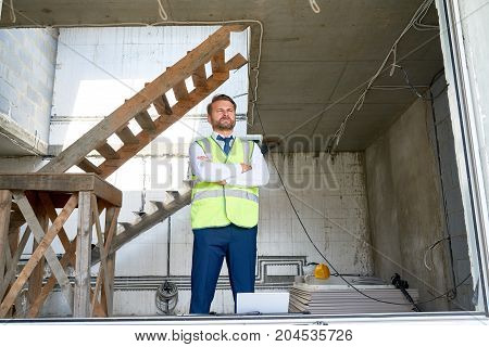 Full length portrait of bearded middle-aged businessman wearing suit and reflective jacket looking away while standing with crossed arms at construction site