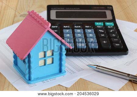 Electronic calculator with push buttons wooden model house metal pen and sheets of paper with the numbers on the table. Payment receipts for services calculation of the construction or purchase of housing. signing of the contract.