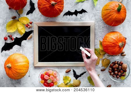 Preparing for halloween. Black desk for notes among pumpkins and bats on grey background top view.
