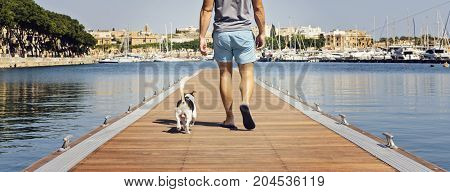 Banner man with a dog walking on the floating pier on a sunny day. Friendship and travel with dog