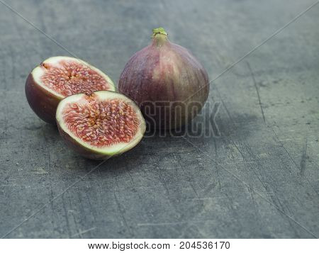 close up one and two half of fresh ripen fig on grey textured background