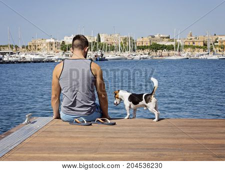 A man with a dog sittnig on the floating pier on a sunny day. Friendship and travel with dog