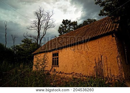 Old Ukrainian village house (mud hut) at sunset on the edge of the forest