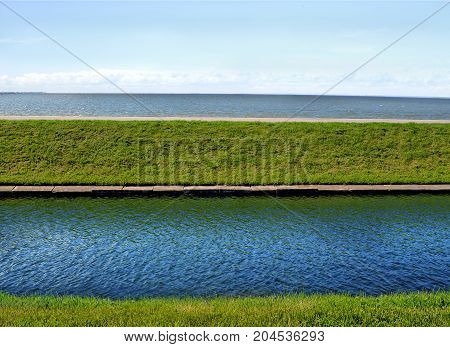 River and sea in parallel with green grass (with a greetings to Andreas Gursky)