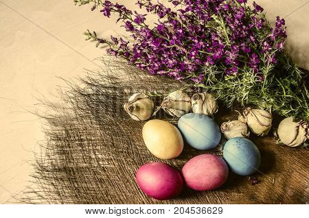 Painted Easter eggs near a bouquet of blooming purple wild flowers on a straw mat