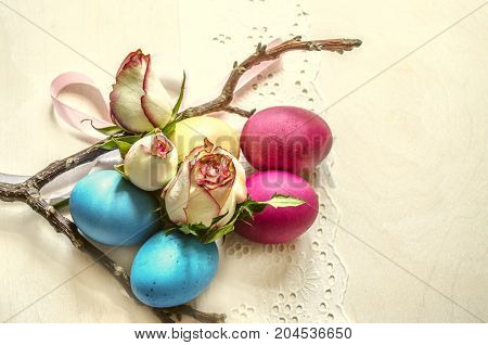 Variegated dyed eggs with rose buds on lace white borderwith dry branch and satin bow on the wooden plywood
