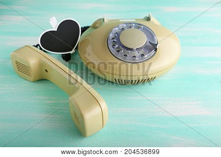 Beige Retro Telephone On Green Wooden Table