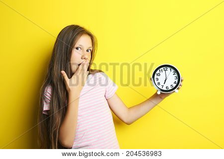 Portrait Of Beautiful Girl With Round Clock On Yellow Background