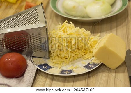 cheese grated on a grater on the table the ingredients