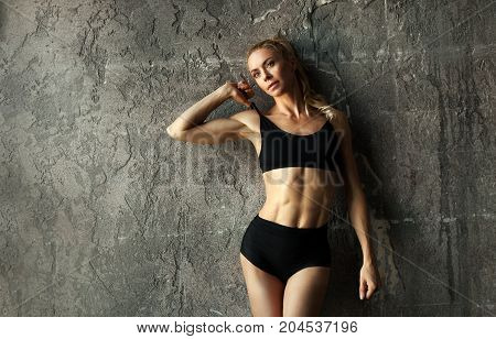 SlimFit female fitness model posing and showing her muscular body with strong and tanned abdominal muscles in front of concrete wall