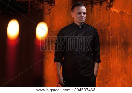 Portrait of handsome catholic priest or pastor with dog collar dark red background. with candles