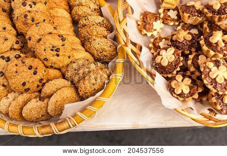 Closeup Of Chocolate Chip Cookies And Biscuits In Wooden Woven Basket
