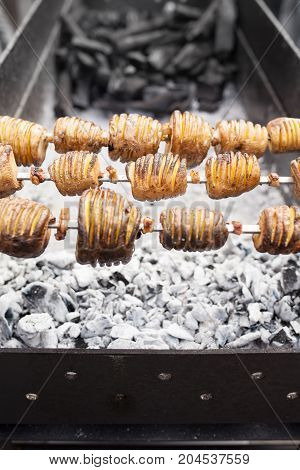 A Shish Kebab From Yellow Potatoes Put On A Skewer Is Fried On Blue Coals