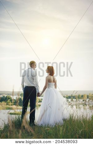 Elegant Gentle Stylish Groom And Bride Near River Or Lake. Wedding Couple In Love