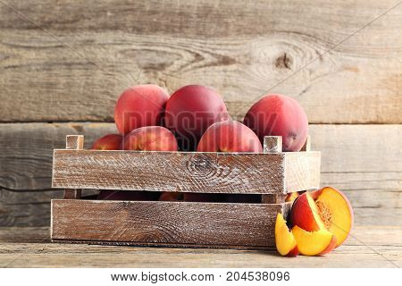 Sweet Nectarines In Crate On Grey Wooden Table