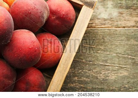 Ripe Nectarines In Crate On Grey Wooden Table