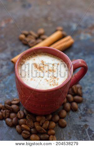 Hot chocolate with cinnamon stick on dark background