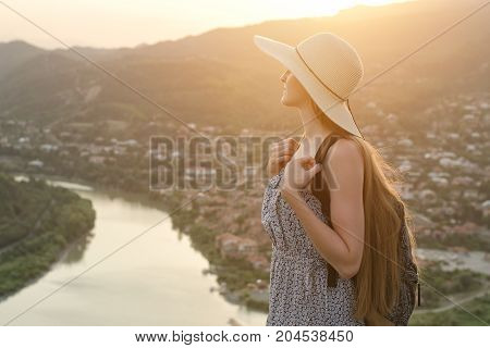 Beautiful Girl With Backpack And Hat Stands Sideways On The Background Of The City And River Below