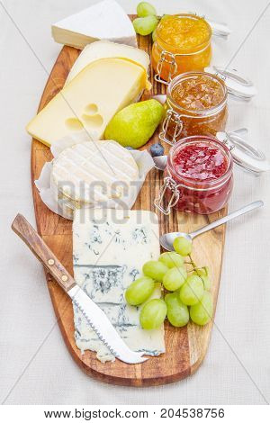 Wooden Cutting Board With Cheese And Jams