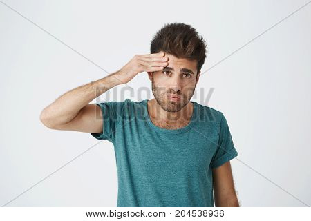 Portrait of young tired caucasian guy wearing blue tshirt wiping his forehead with hand being tired after complex training. Body language