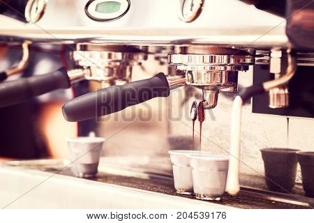 coffee machine. coffee machine preparing fresh coffee and pouring into two cups at restaurant bar or pub toned in vintage style