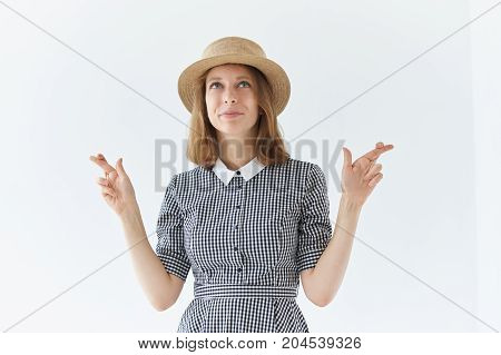 Waist up shot of fashionable cute young woman with short haisrtyle in retro headwear and collar dress looking up with eyes full of hope while making wish hoping for good luck keeping fingers crossed