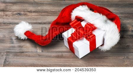 Christmas decoration. Gift box with red ribbon bow on rustic wooden background