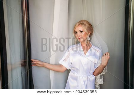 Portrait of a bride in a wedding dress. The bride dresses in the hotel. sunny day