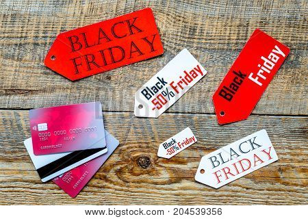 Words black friday on colored labels near bank cards on wooden background top view.