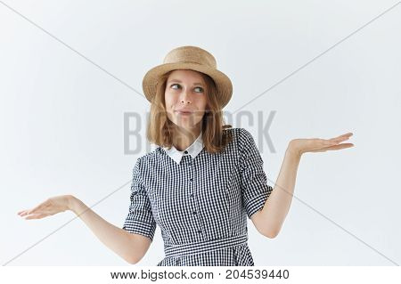 Isolated portrait of beautiful charming young female shrugging shoulders and looking sideways having confused clueless expression on her freckled face don't know what to say. Body language