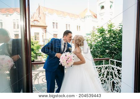 Portrait of a bride in a wedding dress. The bride dresses in the hotel. The groom is dressed at home in a suit. Cute groom posing for a photographer
