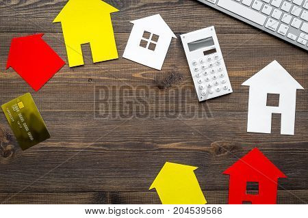 work desk with keyboard and paper house figures for selling house set wooden background top view space for text