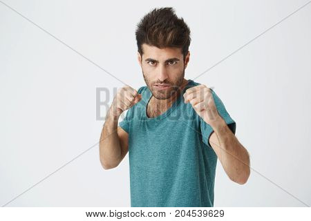 Angry handsome unshaven young spanish man in trendy blue tshirt, trendy haircut, concentrated expression, training with punching bag for boxing competitions