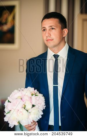 The groom is dressed at home in a suit. Cute groom posing for a photographer. suuny day