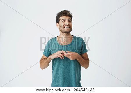 Funny handsome unshaven hispanic man in casual clothes, with good-looking hairstyle, fooling and playing ape on camera. Human face expressions