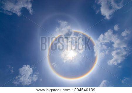 sun corona rainbow clouds and blue sky background Circumscribed halo