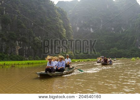 NINH BINH VIETNAM - 5/6/2016: Boats of tourists on the Ngo Dong River near Tam Coc village at the Trang An UNESCO World Heritage site in Ninh Binh Vietnam.