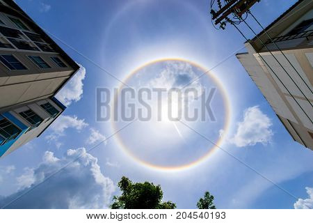 building and sun corona rainbow clouds and blue sky background Circumscribed halo