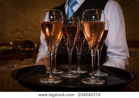 Male waiter welcomes guests with rose sparkling wine on a tray