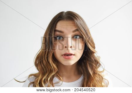 Charming emotional bug-eyed young woman with wavy hair posing in studio with mouth opened being surprised to hear unexpected news. Pretty girl staring at camera in excitement and astonishment