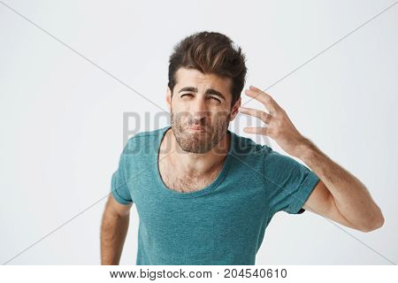 Frustrated attractive bearded caucasian guy in trendy blue tshirt, with grumpy mad expression gesticulating with hand. Human facial expressions and emotions