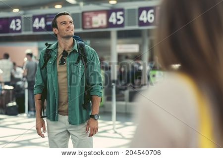 Start of journey. Selective focus of stylish man with backpack is standing in airport and looking up with slight smile. Travel concept