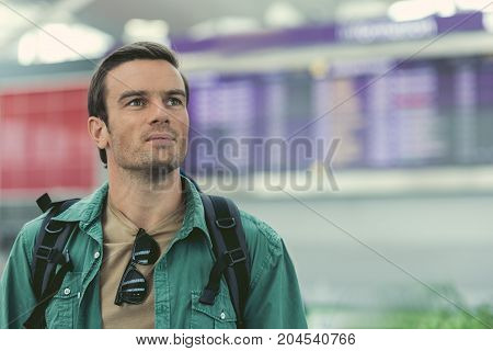 Travel alone. Gorgeous adult man is standing in airport and waiting for registration with information board on background. Copy space in the right side